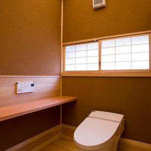 Inredning av ett asiatiskt toalett, med en toalettstol med hel cisternkåpa, bruna väggar, ljust trägolv och orange golv