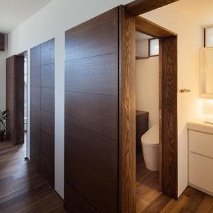 Modelo de aseo de estilo zen con armarios con paneles lisos, sanitario de una pieza, baldosas y/o azulejos blancos, baldosas y/o azulejos de cerámica, paredes blancas, suelo de madera oscura, lavabo encastrado, encimera de acrílico, suelo marrón y encimeras blancas