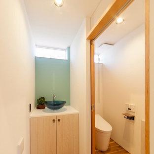 Idées déco pour un WC et toilettes asiatique avec un placard à porte plane, des portes de placard beiges, un mur blanc, un sol en bois brun, une vasque et un sol marron.