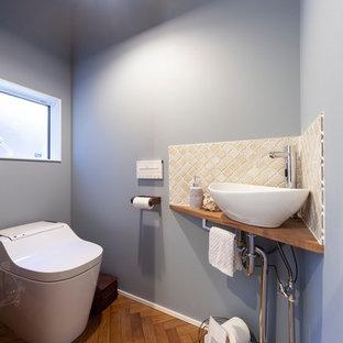 他の地域の北欧スタイルのおしゃれなトイレ・洗面所 (ベージュのタイル、グレーの壁、茶色い床、ベッセル式洗面器、木製洗面台) の写真