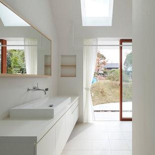 Стильный дизайн: туалет в современном стиле с плоскими фасадами, белыми фасадами, белыми стенами, настольной раковиной, белым полом и белой столешницей - последний тренд