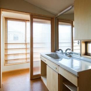Cette photo montre un WC et toilettes moderne avec un placard en trompe-l'oeil, des portes de placard beiges, des plaques de verre, un mur beige, un sol en liège, un lavabo intégré, un plan de toilette en surface solide, un sol marron, un WC suspendu et un plan de toilette beige.