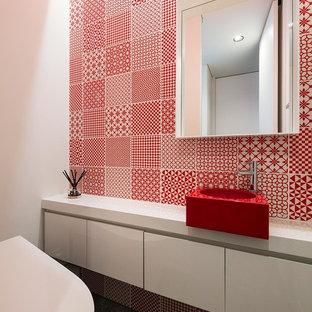 На фото: туалет в стиле модернизм с плоскими фасадами, белыми фасадами, красной плиткой, белыми стенами, настольной раковиной, серым полом и красной столешницей