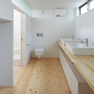 東京23区のモダンスタイルのおしゃれなトイレ・洗面所 (白い壁、無垢フローリング、ベッセル式洗面器、木製洗面台、ベージュの床、ベージュのカウンター) の写真