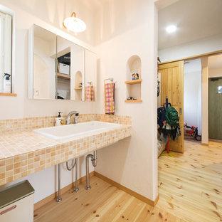 Стильный дизайн: туалет в стиле кантри с оранжевой плиткой, белыми стенами, светлым паркетным полом и разноцветным полом - последний тренд