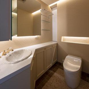 東京23区のトラディショナルスタイルのおしゃれなトイレ・洗面所 (レイズドパネル扉のキャビネット、ベージュのキャビネット、ベージュの壁、オーバーカウンターシンク、グレーの床) の写真