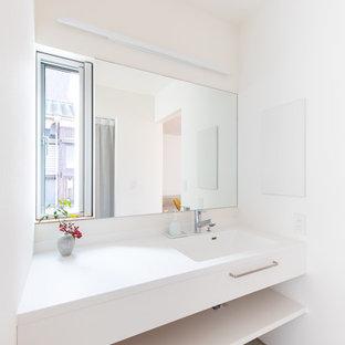 Moderne Gästetoilette mit weißen Schränken, weißer Wandfarbe, Linoleum, integriertem Waschbecken, Mineralwerkstoff-Waschtisch, grauem Boden, weißer Waschtischplatte, flächenbündigen Schrankfronten und schwebendem Waschtisch in Sonstige