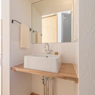 横浜の北欧スタイルのおしゃれなトイレ・洗面所 (白い壁、淡色無垢フローリング、ベッセル式洗面器、木製洗面台、ベージュの床、ベージュのカウンター) の写真