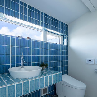 Inspiration for a medium sized modern cloakroom in Other with a one-piece toilet, blue tiles, porcelain tiles, blue walls, porcelain flooring, a vessel sink, tiled worktops, white floors and turquoise worktops.