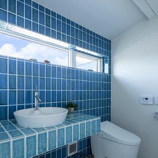 Mittelgroße Moderne Gästetoilette mit Toilette mit Aufsatzspülkasten, blauen Fliesen, Porzellanfliesen, blauer Wandfarbe, Porzellan-Bodenfliesen, Aufsatzwaschbecken, gefliestem Waschtisch, weißem Boden und türkiser Waschtischplatte in Sonstige