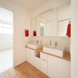 他の地域の北欧スタイルのおしゃれなトイレ・洗面所 (白いキャビネット、白い壁、淡色無垢フローリング、コンソール型シンク、木製洗面台) の写真