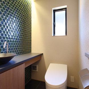 Идея дизайна: маленький туалет в восточном стиле с плоскими фасадами, коричневыми фасадами, унитазом-моноблоком, зеленой плиткой, плиткой мозаикой, белыми стенами, полом из керамической плитки, настольной раковиной, столешницей из ламината, черным полом и черной столешницей