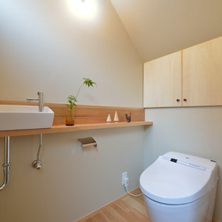 他の地域のアジアンスタイルのおしゃれなトイレ・洗面所 (フラットパネル扉のキャビネット、淡色木目調キャビネット、緑の壁、淡色無垢フローリング、ベッセル式洗面器、ベージュの床、ブラウンの洗面カウンター) の写真