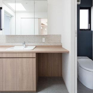 Modelo de aseo vintage con puertas de armario beige, sanitario de una pieza, paredes blancas, suelo de baldosas de porcelana y suelo gris