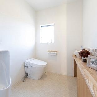 Cette photo montre un WC et toilettes moderne avec des portes de placard en bois brun, un urinoir, un carrelage beige, un carrelage en pâte de verre, un plan de toilette en bois, meuble-lavabo encastré et un plafond en papier peint.