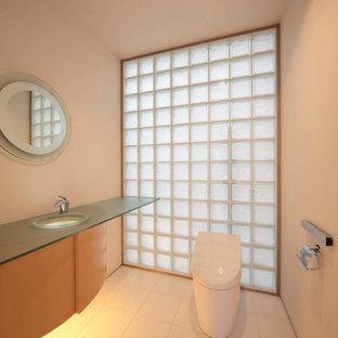 Пример оригинального дизайна: туалет в восточном стиле с плоскими фасадами, светлыми деревянными фасадами, белыми стенами, стеклянной столешницей и белым полом