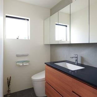 東京23区の小さいモダンスタイルのおしゃれなトイレ・洗面所 (フラットパネル扉のキャビネット、濃色木目調キャビネット、人工大理石カウンター、黒い洗面カウンター、マルチカラーの壁、黒い床) の写真