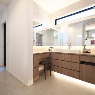 他の地域のモダンスタイルのおしゃれなトイレ・洗面所 (フラットパネル扉のキャビネット、中間色木目調キャビネット、白い壁、ベッセル式洗面器、木製洗面台、グレーの床、ブラウンの洗面カウンター) の写真