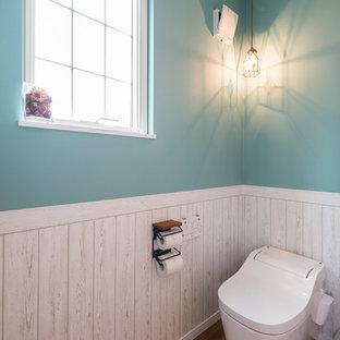 他の地域のビーチスタイルのおしゃれなトイレ・洗面所 (青い壁、無垢フローリング、茶色い床) の写真