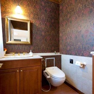 Foto di un bagno di servizio vittoriano con ante con bugna sagomata, ante in legno scuro, pareti multicolore, pavimento in terracotta, lavabo da incasso, pavimento marrone e WC sospeso
