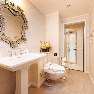 他の地域のトラディショナルスタイルのおしゃれなトイレ・洗面所 (ベージュのタイル、ベージュの壁、テラコッタタイルの床、ペデスタルシンク、茶色い床) の写真