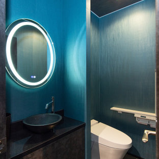 Cette photo montre un grand WC et toilettes moderne avec un placard à porte plane, des portes de placard noires, un WC à poser, un mur bleu, un sol en contreplaqué, une vasque, un plan de toilette en surface solide, un sol noir, un plan de toilette noir, meuble-lavabo sur pied, un plafond en papier peint et du papier peint.
