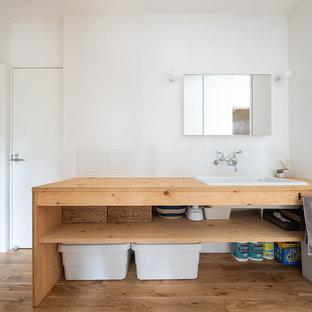 Imagen de aseo asiático con armarios abiertos, paredes blancas, suelo de madera en tonos medios, lavabo encastrado, encimera de madera, suelo marrón y encimeras marrones