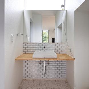 На фото: туалет в скандинавском стиле с белой плиткой, белыми стенами, настольной раковиной, столешницей из дерева, бежевым полом и коричневой столешницей с