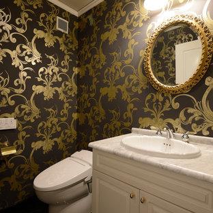 他の地域のトラディショナルスタイルのおしゃれなトイレ・洗面所 (落し込みパネル扉のキャビネット、白いキャビネット、マルチカラーの壁、オーバーカウンターシンク、大理石の洗面台) の写真