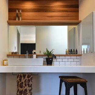 Asiatisk inredning av ett toalett, med vita väggar, ett fristående handfat och grått golv