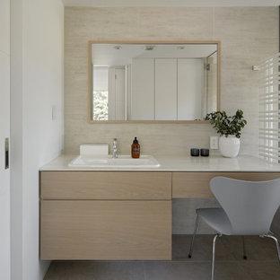 Пример оригинального дизайна: туалет в стиле модернизм с фасадами с декоративным кантом, бежевыми фасадами, бежевой плиткой, керамической плиткой, бежевыми стенами, полом из керамогранита, накладной раковиной, столешницей из искусственного камня и бежевой столешницей