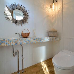 他の地域のビーチスタイルのおしゃれなトイレ・洗面所 (白い壁、無垢フローリング、オーバーカウンターシンク、茶色い床) の写真