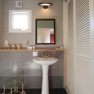 На фото: туалеты в стиле модернизм с фасадами с филенкой типа жалюзи, белыми фасадами, серой плиткой, плиткой мозаикой, серыми стенами, полом из цементной плитки, раковиной с пьедесталом и черным полом