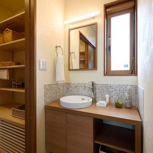 他の地域のモダンスタイルのおしゃれなトイレ・洗面所 (中間色木目調キャビネット、マルチカラーのタイル、石タイル、白い壁、無垢フローリング、木製洗面台、ベッセル式洗面器、茶色い床) の写真
