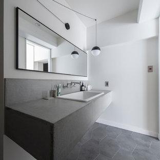 Ejemplo de aseo industrial, de tamaño medio, con armarios abiertos, paredes blancas, suelo vinílico, lavabo bajoencimera, encimera de cemento, suelo gris y encimeras grises
