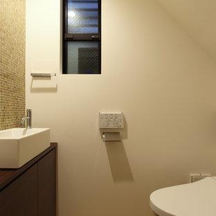 На фото: маленькие туалеты в восточном стиле с плоскими фасадами, коричневыми фасадами, унитазом-моноблоком, коричневой плиткой, плиткой из листового стекла, белыми стенами, настольной раковиной, бежевым полом и коричневой столешницей
