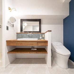 Свежая идея для дизайна: туалет в стиле модернизм с открытыми фасадами, унитазом-моноблоком, синей плиткой, плиткой мозаикой, белыми стенами, полом из винила, врезной раковиной, столешницей из дерева, серым полом и коричневой столешницей - отличное фото интерьера