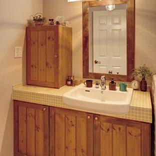 他の地域のカントリー風おしゃれなトイレ・洗面所 (落し込みパネル扉のキャビネット、中間色木目調キャビネット、ベージュの壁、無垢フローリング、タイルの洗面台、茶色い床) の写真
