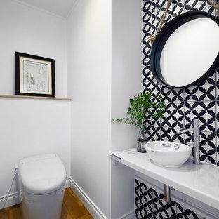 東京23区のトランジショナルスタイルのおしゃれなトイレ・洗面所 (一体型トイレ、モノトーンのタイル、白い壁、無垢フローリング、ベッセル式洗面器、茶色い床、白い洗面カウンター) の写真