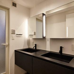 Réalisation d'un WC et toilettes design de taille moyenne avec un placard à porte plane, des portes de placard noires, un carrelage blanc, un mur blanc, un sol en linoléum, un lavabo intégré, un plan de toilette en zinc, un sol marron, un plan de toilette noir, meuble-lavabo sur pied, un plafond en lambris de bois et du lambris de bois.
