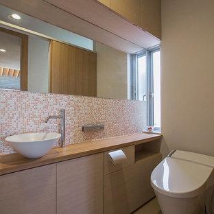 Стильный дизайн: туалет в современном стиле с плоскими фасадами, бежевыми фасадами, оранжевой плиткой, розовой плиткой, белой плиткой, плиткой мозаикой, серыми стенами, настольной раковиной, столешницей из дерева, серым полом и коричневой столешницей - последний тренд