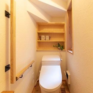 Esempio di un bagno di servizio nordico con pareti bianche, pavimento in legno massello medio e pavimento marrone