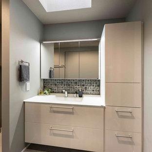 他の地域の中くらいのモダンスタイルのおしゃれなトイレ・洗面所 (フラットパネル扉のキャビネット、白いキャビネット、グレーのタイル、グレーの壁、一体型シンク、人工大理石カウンター、グレーの床、白い洗面カウンター) の写真