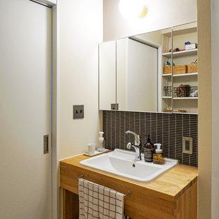 Foto de aseo de estilo zen con armarios abiertos, puertas de armario de madera oscura, baldosas y/o azulejos negros, baldosas y/o azulejos en mosaico, paredes beige, lavabo encastrado, encimera de madera y encimeras marrones
