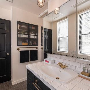 横浜のトラディショナルスタイルのおしゃれなトイレ・洗面所 (落し込みパネル扉のキャビネット、黒いキャビネット、白い壁、オーバーカウンターシンク、グレーの床) の写真