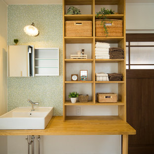 Design ideas for a world-inspired cloakroom in Other with green tiles, mosaic tiles, white walls, a vessel sink, wooden worktops, brown floors and brown worktops.