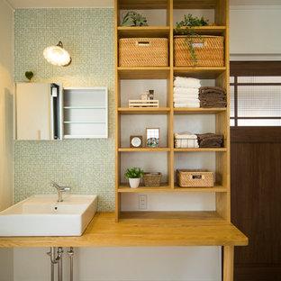 Diseño de aseo de estilo zen con baldosas y/o azulejos verdes, baldosas y/o azulejos en mosaico, paredes blancas, lavabo sobreencimera, encimera de madera, suelo marrón y encimeras marrones