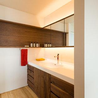 Modelo de aseo asiático con armarios con paneles lisos, puertas de armario de madera oscura, paredes blancas, suelo de madera en tonos medios, lavabo integrado y suelo marrón