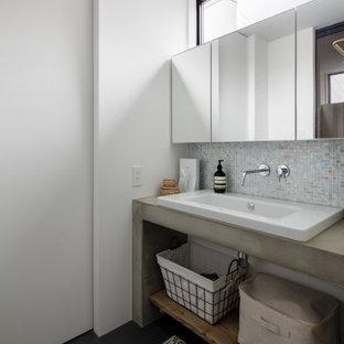 他の地域のコンテンポラリースタイルのおしゃれなトイレ・洗面所 (マルチカラーのタイル、モザイクタイル、赤い壁、オーバーカウンターシンク、コンクリートの洗面台、黒い床、グレーの洗面カウンター) の写真