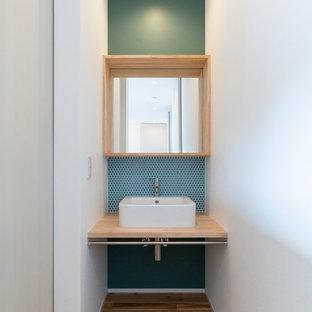 Foto på ett litet nordiskt beige toalett, med öppna hyllor, skåp i ljust trä, grön kakel, mosaik, vita väggar, mellanmörkt trägolv, ett fristående handfat, träbänkskiva och beiget golv